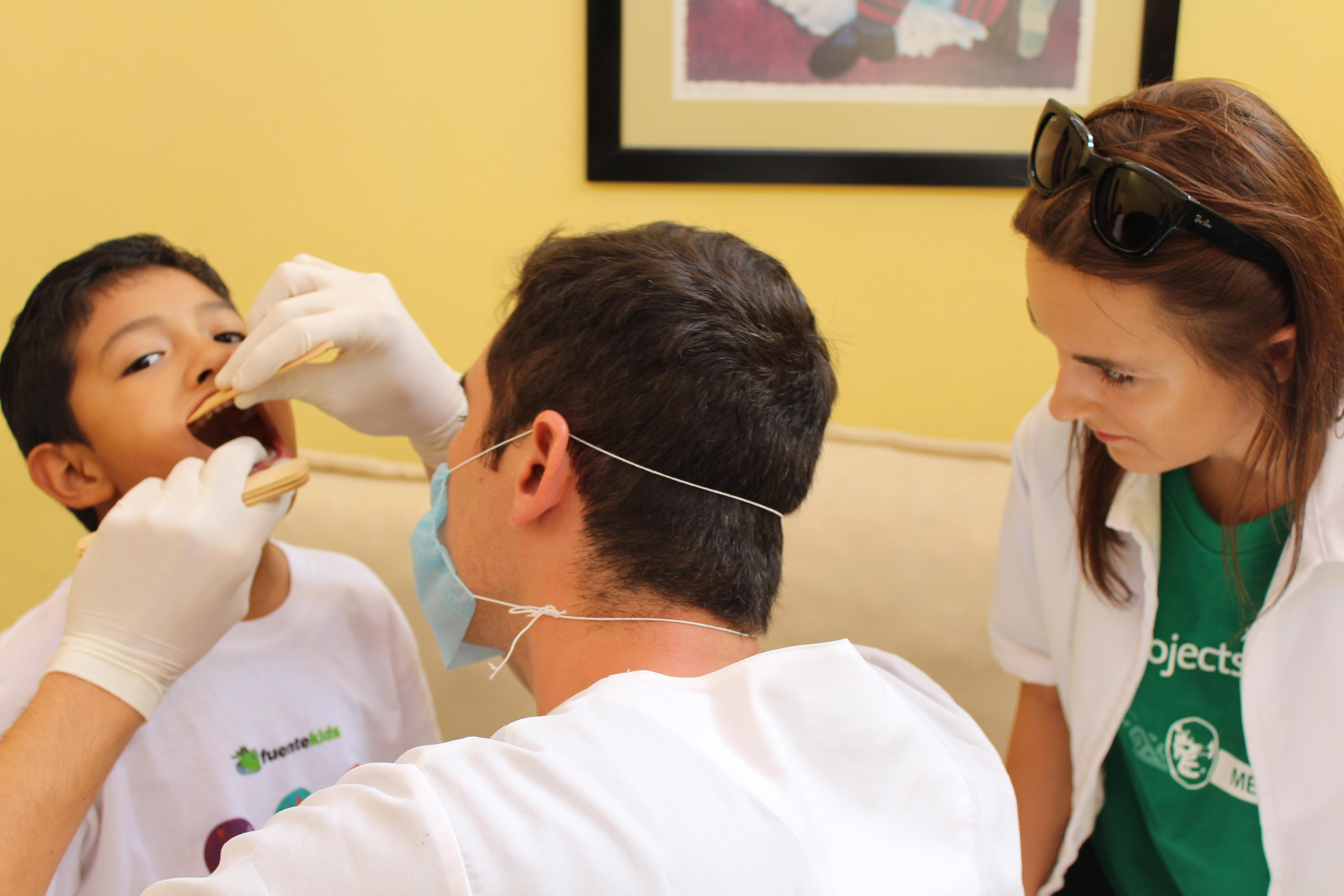 Male Dentistry intern examines a patient's mouth in a Healthcare centre during a Dentistry internship in Mexico.